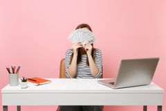 Young woman covering face with bundle lots of dollars, cash money working at office at white desk with pc laptop. Isolated on pastel pink background stock photo