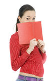 Young woman covering face by red book Stock Photo