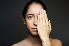 Young woman covering half of her face with a hand. Stock Photography