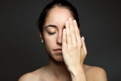 Young woman covering half of her face with a hand. Royalty Free Stock Photography