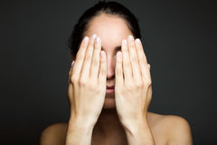 Young woman covering half of her face with a hand. Stock Image