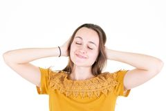 Young woman covering with hands her ears isolated on white background. A young woman covering with hands her ears isolated on white background royalty free stock image