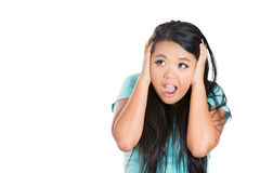 Young woman covering her ears looking up, as if to say, stop making that loud noise it's giving me a headache Royalty Free Stock Image