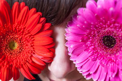 Young woman covering her eyes with fresh colorful flowers. Macro Stock Images