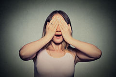 Young woman covering her eyes with hands doesn't see Stock Images