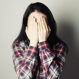 Young woman covering her eyes with her hands. Stock Images