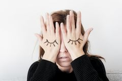 Young woman is covering her eyes with her palms. Eyes painted on her hand. Royalty Free Stock Photos