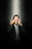 Young woman covering her eyes in a ray of light Royalty Free Stock Image