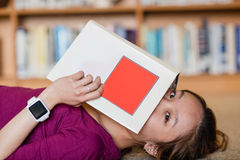 Young woman covering her face with book Stock Photography