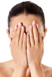 Young woman covering her face with her hands. Stock Image