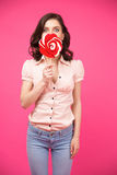 Young woman covering her face with lollipop Stock Image