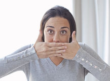Young woman covering her mouth with both hands Royalty Free Stock Photos