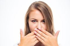 Young woman covering her mouth. With hands isolated on a white background Royalty Free Stock Images
