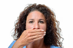 Young woman covering her mouth with her hand. Serious young woman with long curly hair covering her mouth with her hand in a Speak No Evil concept, head shot  on Stock Images