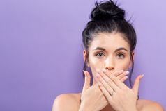 Young woman covering her mouth. On a solid background Royalty Free Stock Images