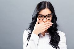 Young woman covering her mouth. On a solid background Royalty Free Stock Image
