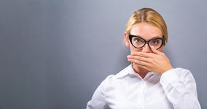 Young woman covering her mouth. On a solid background Royalty Free Stock Photography