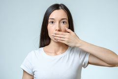 Young woman covering her mouth. On white Stock Image