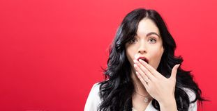 Young woman covering her mouth. On a solid background Stock Image