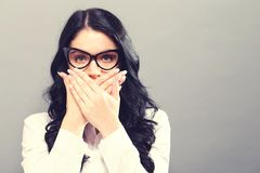 Young woman covering her mouth. On a solid background Royalty Free Stock Photos