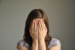 A young woman covers her face with hands Royalty Free Stock Image