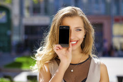 Young woman covers her face screen smartphone Royalty Free Stock Photos