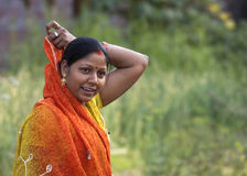 Young woman covers her hair with orange sari. Stock Photography