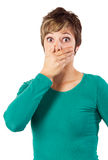 Young woman covers her mouth. Shocked woman in green sweatshirt covering her mouth with her hand. Studio shot against a white background Royalty Free Stock Images