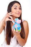Young woman with a cow piggy bank Stock Photo