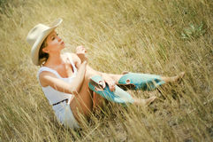 Young woman in a cowboy hat and boots. Young woman in cowboy hat and boots sitting in the yellow grass, summer outdoor full length portrait Stock Photography