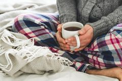 Young woman in cozy pyjamas and gray cardigan sitting on a bed with a mug of tea Stock Images
