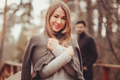 Young woman in cozy warm cardigan walking outdoor in autumn forest, with boyfriend on background Royalty Free Stock Image