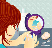 Young woman with cream in the mirror. Young women putting cream on face looking at the mirror Royalty Free Stock Image