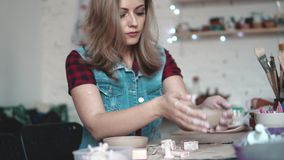 Young woman creates a plate of clay in the workshop. girl holding a shape of clay in her hands. the creative hobby.  stock video footage