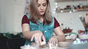 Attractive young Caucasian woman spends time behind a creative hobby. the girl enthusiastically sculpts a plate of clay. Young woman creates a plate of clay in stock footage