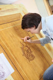 Young woman creating artwork in wood Stock Images