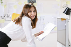 Young woman creative designer with documents working in office. Stock Images