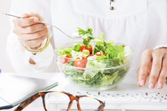 Young woman creative designer eating a salad while working in office. royalty free stock photo