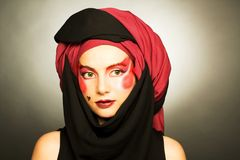 Young woman with creative make-up. In black and red turban Royalty Free Stock Photography