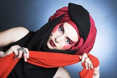 Young woman with creative make-up. In black and red turban Stock Photos