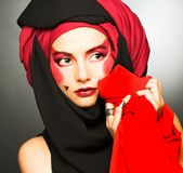 Young woman with creative make-up. In black and red turban Stock Image