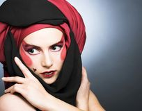 Young woman with creative make-up. In black and red turban Stock Images