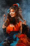 Woman with creative make-up in doll style with candy. Young woman with creative make-up in doll style with candy.Over smoke background stock photos