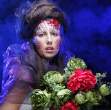young woman with creative make up holding flowers Stock Photography