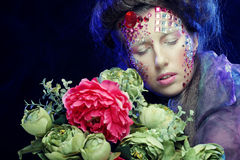 young woman with creative make up holding flowers Royalty Free Stock Images