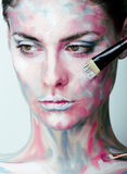 Young woman with creative make up like painted oil Stock Image