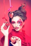 Young woman with creative make-up. With red and pink hearts Royalty Free Stock Photos