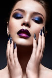 Young woman with creative make-up and violet lips with a gradient and sparkles on the face. Beautiful model with bright nails with Stock Image