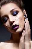 Young woman with creative make-up and violet lips with a gradient and sparkles on the face. Beautiful model with bright nails with Royalty Free Stock Photography
