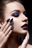Young woman with creative make-up and violet lips with a gradient and sparkles on the face. Beautiful model with bright nails with. Rhinestones. The beauty of Stock Photography